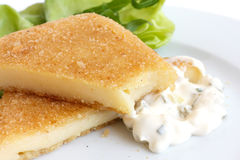 Fried cheese, cut and melting with tartar sauce and salad. Stock Photo