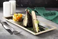 Fried cheese in nori leaves and breadcrumbs with vegetable tartare. Delicious food with beautiful presentation for restaurant menu stock photography