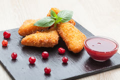 Fried cheese sticks served with cranberries, sauce on black ston Stock Image