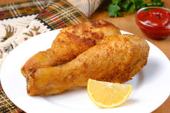 Fried chicken. Legs with lemon and ketchup on the white plate Stock Photography