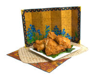 Fried Chicken. Plate of fried chicken on placemat with decorative screen isolated over white background Royalty Free Stock Images
