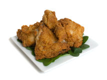 Fried Chicken. Pieces on china plate isolated over white background royalty free stock image