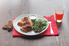 Fried chicken with salad, bread and juice. Fried chicken with arugula in white plate on wooden table Royalty Free Stock Images