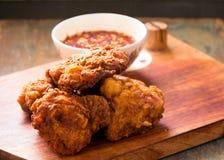 Fried Chicken avec de la sauce chaude sur un conseil en bois Photographie stock libre de droits
