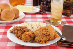 Fried chicken and baked beans on a picnic table Royalty Free Stock Photo