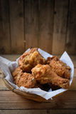 Fried Chicken in a basket. On a wooden floor Royalty Free Stock Photos
