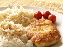 Fried chicken brease. Fried chicken breast filet with sauerkraut, rice and tomatoes stock photo