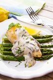 Fried chicken breast on asparagus with tarragon and mushroom sauce Stock Images