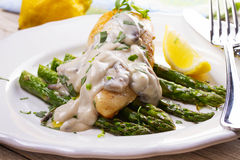 Fried chicken breast on asparagus with tarragon and mushroom sauce Stock Photography