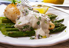 Fried chicken breast on asparagus with tarragon and mushroom sauce Royalty Free Stock Photography