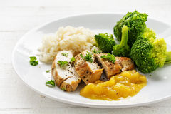Fried chicken breast fillet with fruity mango sauce, broccoli an Stock Photo