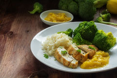 Fried chicken breast fillet with stewed fruit sauce, broccoli an Stock Photo