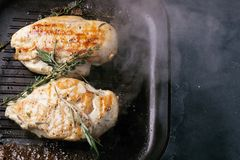 Fried chicken breast with rosemary on the grill pan with smoke. Top view. Copy space royalty free stock photo