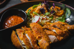 Fried Chicken with chili sauce and salad of radish, sprout, onio Royalty Free Stock Image