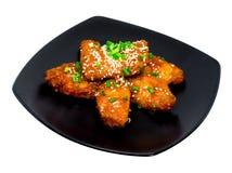 Fried Chicken com molho coreano no prato preto Fotografia de Stock Royalty Free