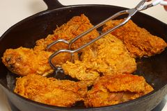 Fried Chicken Cooking in a Frying Pan. Closeup view of chicken pieces frying in a cast-iron skillet royalty free stock images