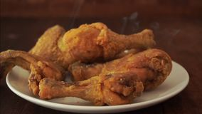 Fried chicken dropped into plate stock footage