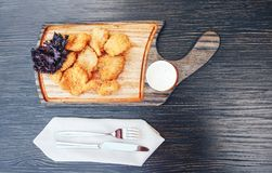 Fried chicken drumstick on a cutting wooden board. wooden background stock images