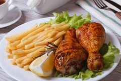 Fried chicken drumsticks with french fries, rosemary and lemon Royalty Free Stock Photos