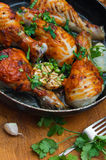 Fried chicken drumsticks in a frying pan. On wooden table Stock Photo