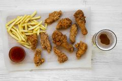 Fried chicken drumsticks, spicy wings, French fries and chicken strips with sour-sweet sauce and cold beer over white wooden backg. Round, top view. Flat lay royalty free stock images