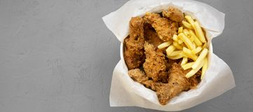 Fried chicken drumsticks, spicy wings, French fries and chicken strips in a paper box over gray background, top view. Flat lay,. From above, overhead. Copy royalty free stock photography