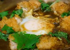 Fried chicken with egg in miso soup serve on hot stone bowl,. Japanese food. image for background, wallpaper and copy space royalty free stock image