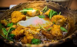 Fried chicken with egg in miso soup serve on hot stone bowl. Japanese food. image for background, wallpaper and copy space royalty free stock photography