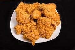 Fried Chicken en la placa negra cuadrada y el fondo negro Fotos de archivo libres de regalías