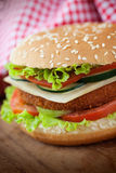 Fried chicken or fish burger sandwich. Junk food concept. Deep fried chicken or fish burger sandwich with lettuce, tomato, cheese and cucumber on wooden stock photography