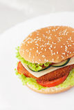 Fried chicken or fish burger sandwich. Junk food concept. Deep fried chicken or fish burger sandwich with lettuce, tomato, cheese and cucumber on wooden Stock Image