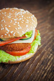 Fried chicken or fish burger sandwich. Junk food concept. Deep fried chicken or fish burger sandwich with lettuce, tomato, cheese and cucumber on wooden Stock Photo