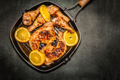 Fried chicken. On grill pan with sliced oranges Stock Image
