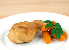 Fried chicken leg with baby carrots Stock Images