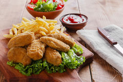 Fried chicken leg in breadcrumbs and french fries Stock Images