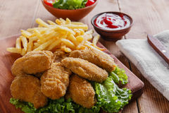 Fried chicken leg in breadcrumbs and french fries Royalty Free Stock Images
