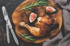 Fried chicken leg with a crispy crust with figs and rosemary. Stock Image