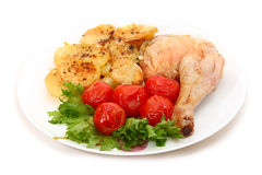 Fried chicken leg with potatoes and marinated tomatoes. On white background Royalty Free Stock Photos