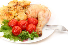 Fried chicken leg with potatoes and marinated tomatoes. On white background Stock Photo