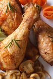 Fried chicken legs with mushrooms and vegetables macro top view Royalty Free Stock Images