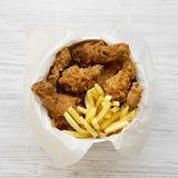 Fried chicken legs, spicy wings, French fries and chicken strips in paper box over white wooden background, overhead view. Flat la. Y, top view, from above royalty free stock photo