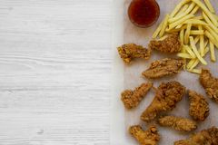 Fried chicken legs, spicy wings, French fries and chicken strips with sour-sweet sauce over white wooden background, top view. Fla. T lay, overhead, from above royalty free stock images