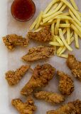 Fried chicken legs, spicy wings, French fries and chicken strips with sour-sweet sauce over white wooden surface, view from above. Flat lay, overhead, top view royalty free stock photo