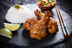 Fried chicken legs with teriyaki sauce sesame seeds and rice on  black stone Stock Photo