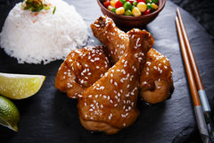 Fried chicken legs with teriyaki sauce sesame seeds and rice on  black stone Royalty Free Stock Images