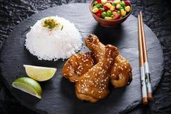 Fried chicken legs with teriyaki sauce sesame seeds  rice on black stone Stock Image