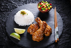 Fried chicken legs with teriyaki sauce sesame seeds  rice on black stone Royalty Free Stock Images