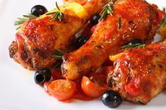 Fried chicken legs in tomato sauce with peppers on a plate macro Royalty Free Stock Photography
