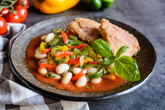 Fried chicken legs with white bean, vegetable and tomato sauce. Fried chicken legs with white bean, tricolor bell pepper and tomato sauce royalty free stock photo