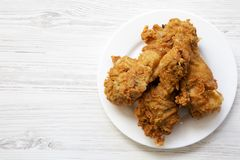 Fried chicken legs on a white round plate with copy space, top view. From above, overhead. Flat lay stock images
